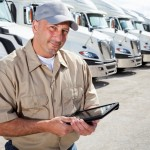 Truck driver (30s) standing in front of row of semi-trucks using digital tablet.
